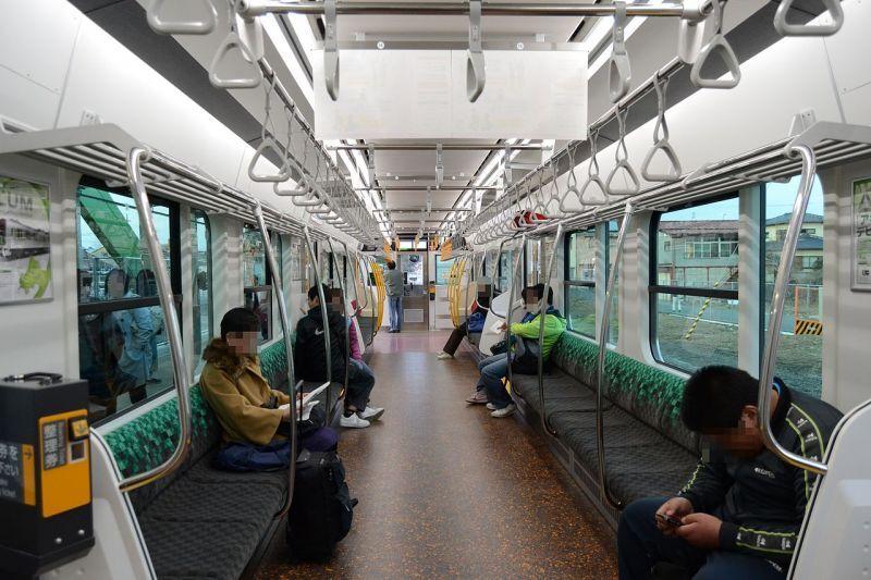 空いている電車で離れて座る乗客(公共距離・近接相、相互認識域)