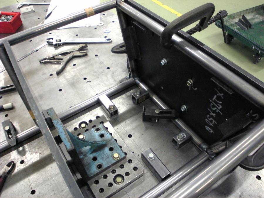 定盤と治具を組み合わせてパイプを位置決めし、溶接などで接合する